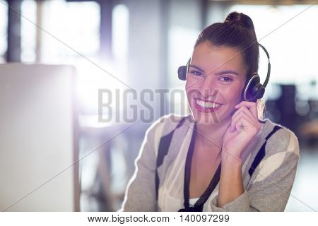 Portrait of smiling young woman with headphones in office
