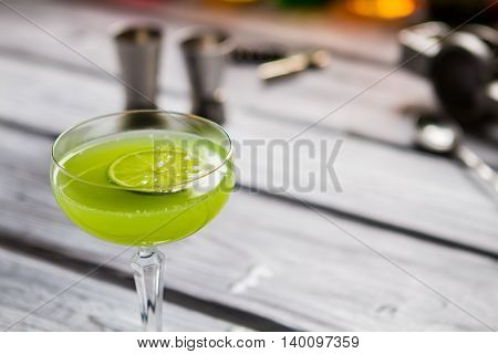 Green drink in glass. Slice of lime in beverage. Alcoholic cocktail with rum. Proven recipe of kiwi daiquiri.