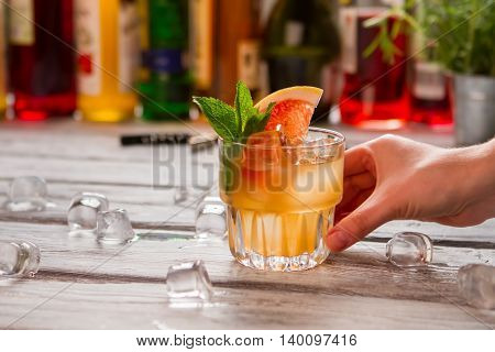 Beverage with slice of grapefruit. Hand touches glass with drink. Refreshing cold cocktail. Whiskey and fruit juice.