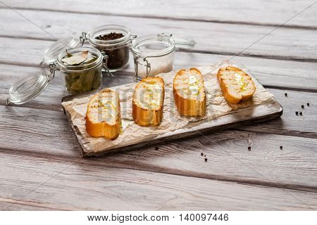 Slices of bread with oil. Jar with salt. Prepare delicious snack at home. Crispy grilled baguette.