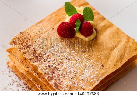 Pastry with raspberries. Small leaves of mint. How to prepare millefeuille. Powdered sugar and chocolate crumbs.