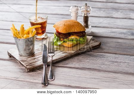 Hamburger and cutlery. Cola pours into glass. Meal on diner table. Cool beverage and hot food.