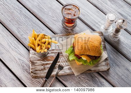 Hamburger and glass of cola. Fries and salt with pepper. Tasty snack with chilled drink. Welcome to our diner.