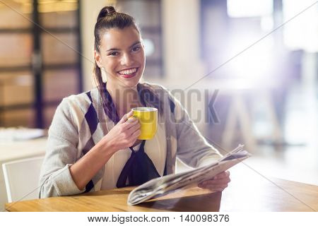Portrait of smiling young woman holding newspaper and coffee cup in office