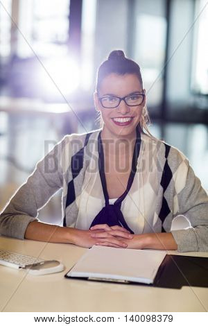 Portrait of smiling young woman sitting by table in office