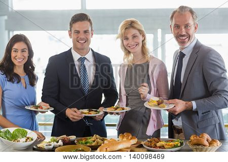 Portrait of business colleagues serving themselves at buffet lunch in a restaurant