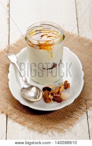 greek yogurt with nuts and sweet honey in a glass on plate