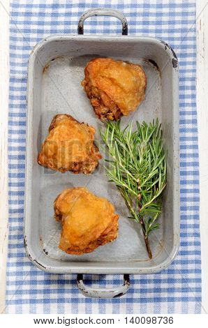fried chicken thigh with rosemary in a roasting tin