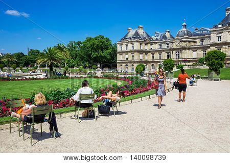 Paris France - Jule 07 2016: People enjoy sunny day in the Luxembourg Garden in Paris. Luxembourg Palace is the official residence of the French Senate.