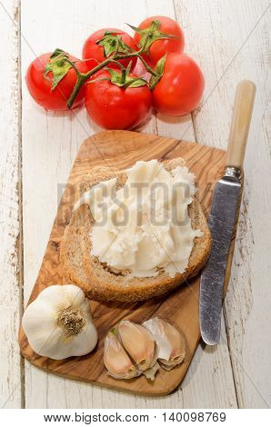 homemade pork lard with coarse salt garlic and fresh tomato on a wooden board