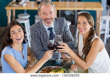 Portrait of businessman and colleague toasting glasses of wine in restaurant