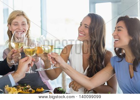 Happy female colleagues toasting beer glasses while having lunch in a restaurant