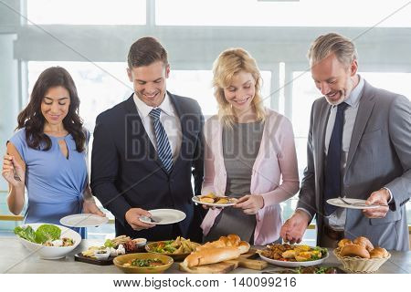 Business colleagues serving themselves at buffet lunch in a restaurant