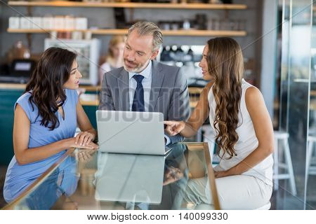Business colleagues discussing over a laptop in the restaurant
