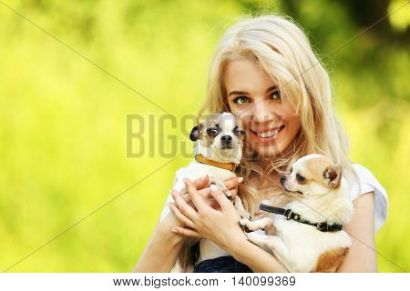 Woman holding fluffy dogs in the park
