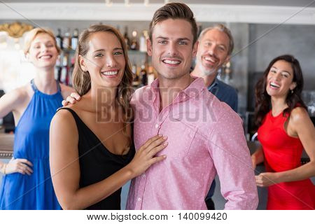 Portrait couple embracing each other in restaurant and friends standing in background