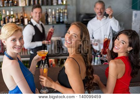 Portrait of happy female friends holding glass of cocktail at bar counter in restaurant