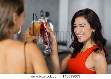 Two beautiful women having cocktail in restaurant