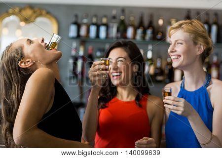 Female friends having tequila shot in restaurant
