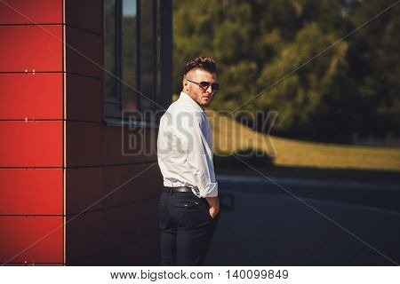 Portrait of a young handsome man model of fashion wearing shirt and glasses in urban background