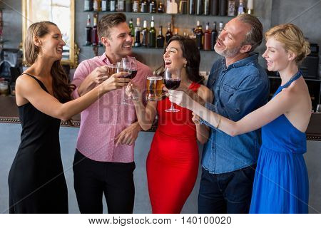 Group of friends toasting glasses of beer and wine in restaurant