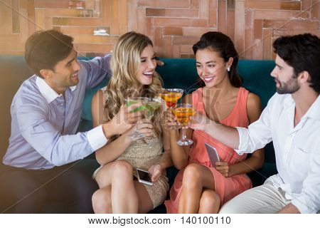 Group of friends toasting glasses of cocktail in restaurant