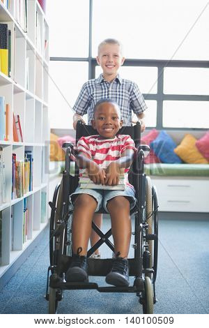 Portrait of happy schoolboy carrying his friend in wheelchair at library