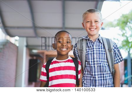Portrait of smiling schoolkids standing in corridor at school