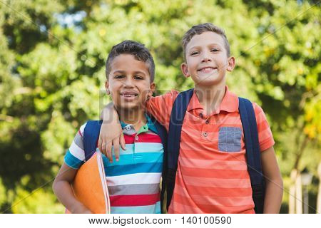 Portrait of smiling schoolkids standing with arm around in campus at school