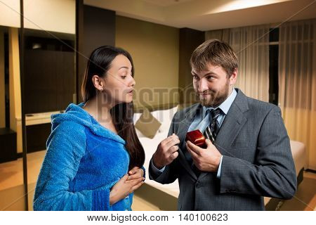 Businessman putting a gift-box in the pocket, woman is interested in it