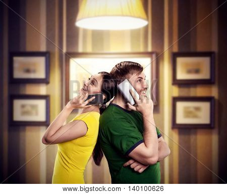 Happy man and woman talking by mobile phones standing back to back