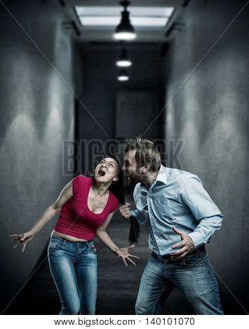 Man and woman fighting in dark corridor