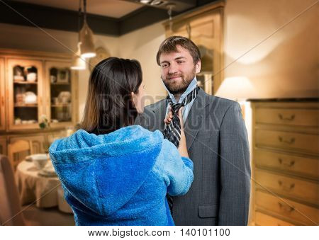 Young wife tieing a tie to her smiling husband