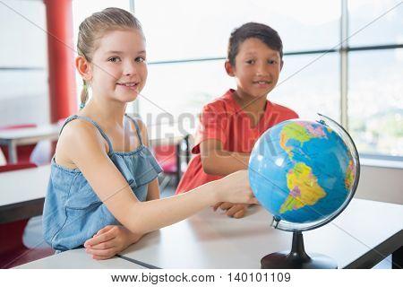 Portrait of school kids studying globe in classroom at school