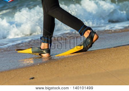 Surfing surfer body board rider entering beach ocean closeup flippers swimming fins.