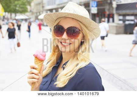 Woman with straw hat eating ice-cream in the city