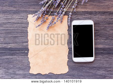 Old paper and smart phone with lavender flower on dark wooden table background. top view with copy space