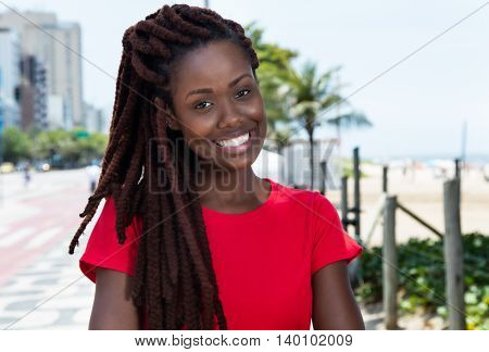 Laughing african woman with dreadlocks outdoor in city in summer