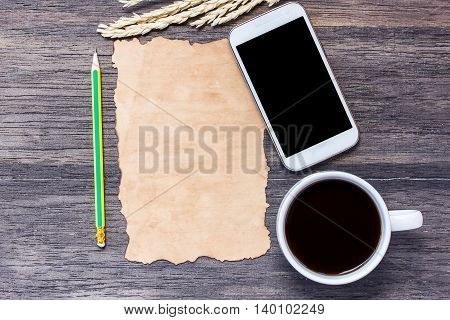 Ears of wheatsmart phone and old paper with cup of coffee on dark wooden table background. top view with copy space