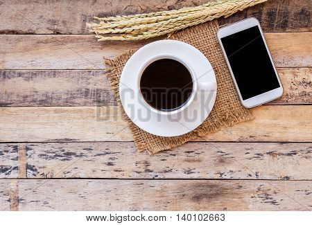 Ears of wheat and cup of coffee with smart phone on a wooden table background. Top view with copy space