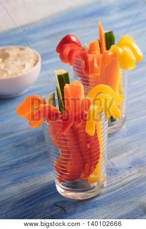 Colorful vegetable sticks in two glasses on blue background