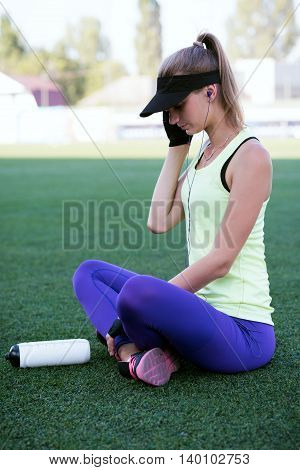 Sporty girl speaks by phone. Football stadium. Slim sporty fitness woman. Bottle Shaker protein. Social media and fitness concept. Toned image.