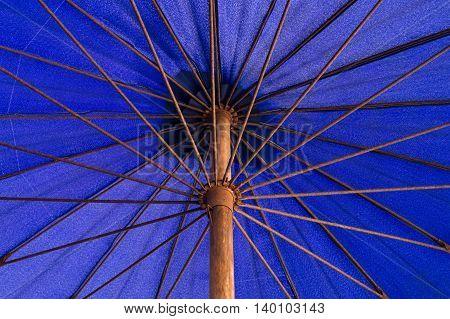 Under a long-handled blue umbrella nylon .