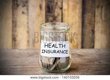 Save money for HEALTH INSURANCE concept money in the glass with filter effect retro vintage style