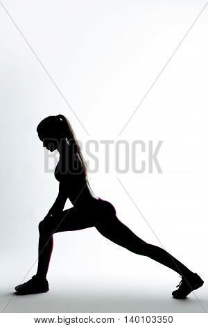 Young woman doing flexibility stretching exercise. Dark silhouette over gray background