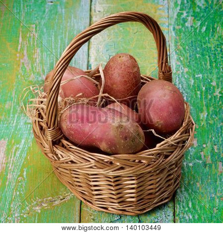Arrangement of Fresh Raw Red Potatoes in Wicker Basket closeup on Cracked Wooden background