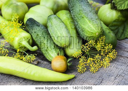 Harvest of fresh cucumbers on the wooden background