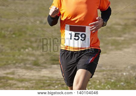 Athletic runner on a cross country race. Outdoor circuit. Horizontal
