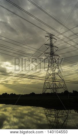 High voltage pylons on the rice field in the evening at sunset .