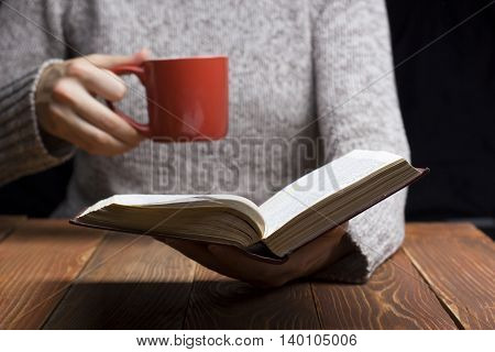 Young woman reading a book and holding cup of tea or coffee. Toned image.